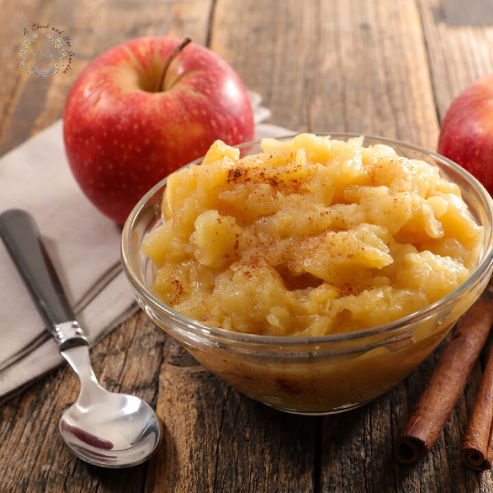 cinnamon applesauce in a glass dish on a wooden table with two apples, a spoon, napkin and cinnamon sticks