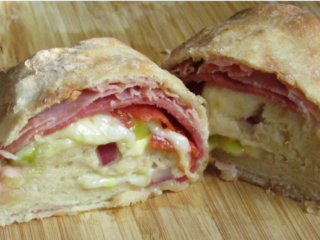 Stromboli cut in half showing the fillings on a wooden cutting board