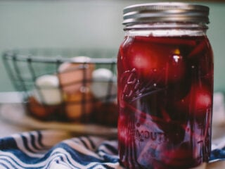 mason jar of pickled beet eggs on a blue an white towel with a wire basket of eggs in the background
