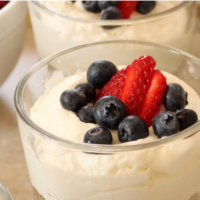 close up of an individual no-bake cheesecake in a mini trifle bowl with fresh berries on top