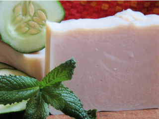 white soap with a sprig of mint and a slice of cucumber