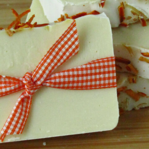 one bar of white soap with dried orange peels on top wrapped in orange gingham ribbon leaning against two stacked bars of soap