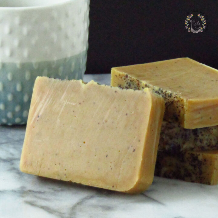 four bars of pumpkin coffee soap stacked on a marble surfacewith a blue and white mug in the background
