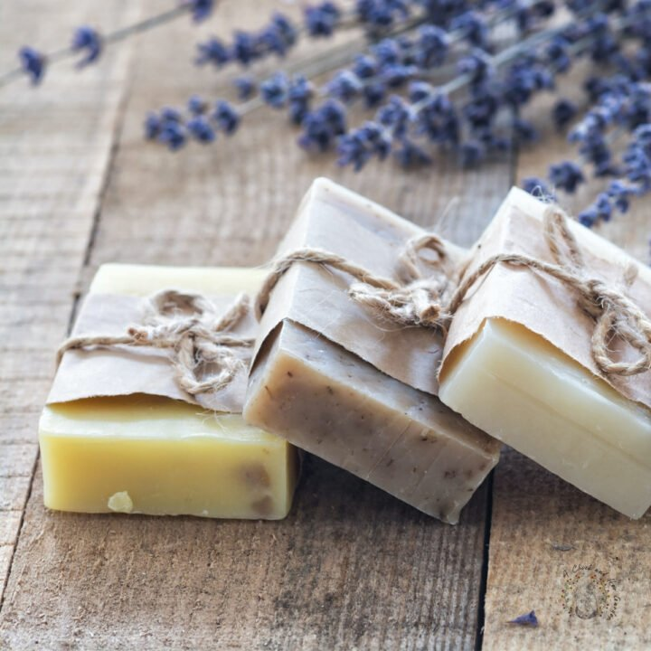 three bars of artisan soap wrapped in paper and twine on a wooden surface with lavender in the background