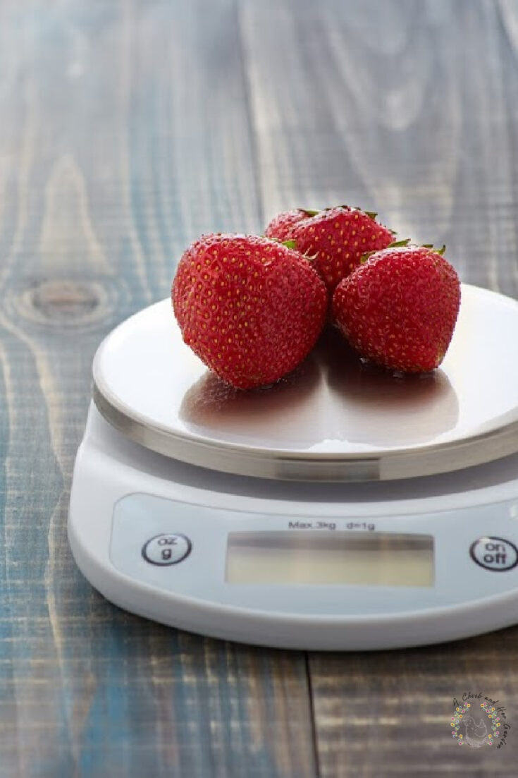 Three ripe strawberries sitting on electronic kitchen scale on a wooden surface