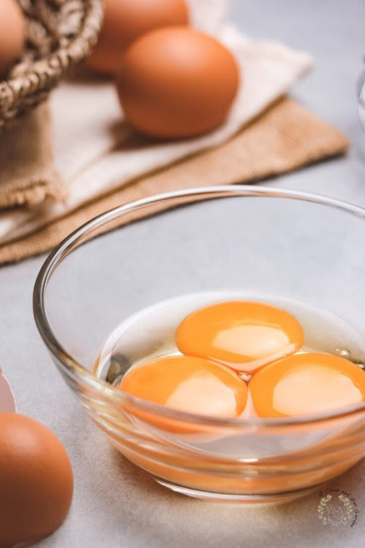 small glass dish holding three egg yolks with eggs on a dish towel in the background