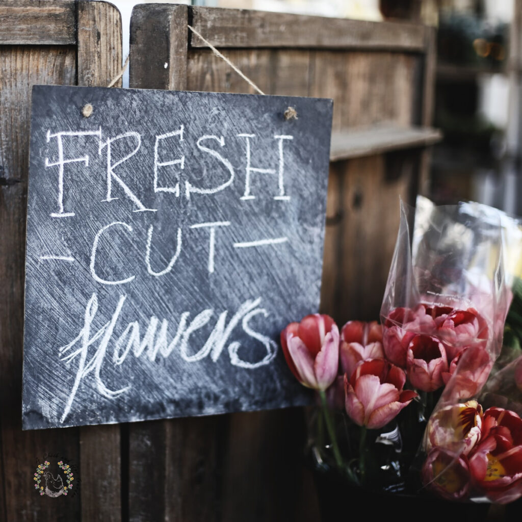 chalkboard sign reading fresh cut flowers hanging on a wooden backdrop next to bouquets of fresh cut tulips