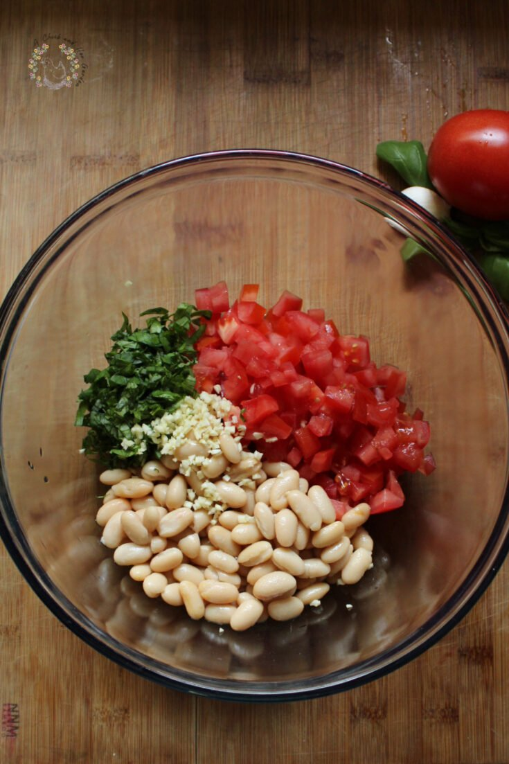 glass bowl with diced tomatoes, cannellini beans, chopped basil and minced garlic