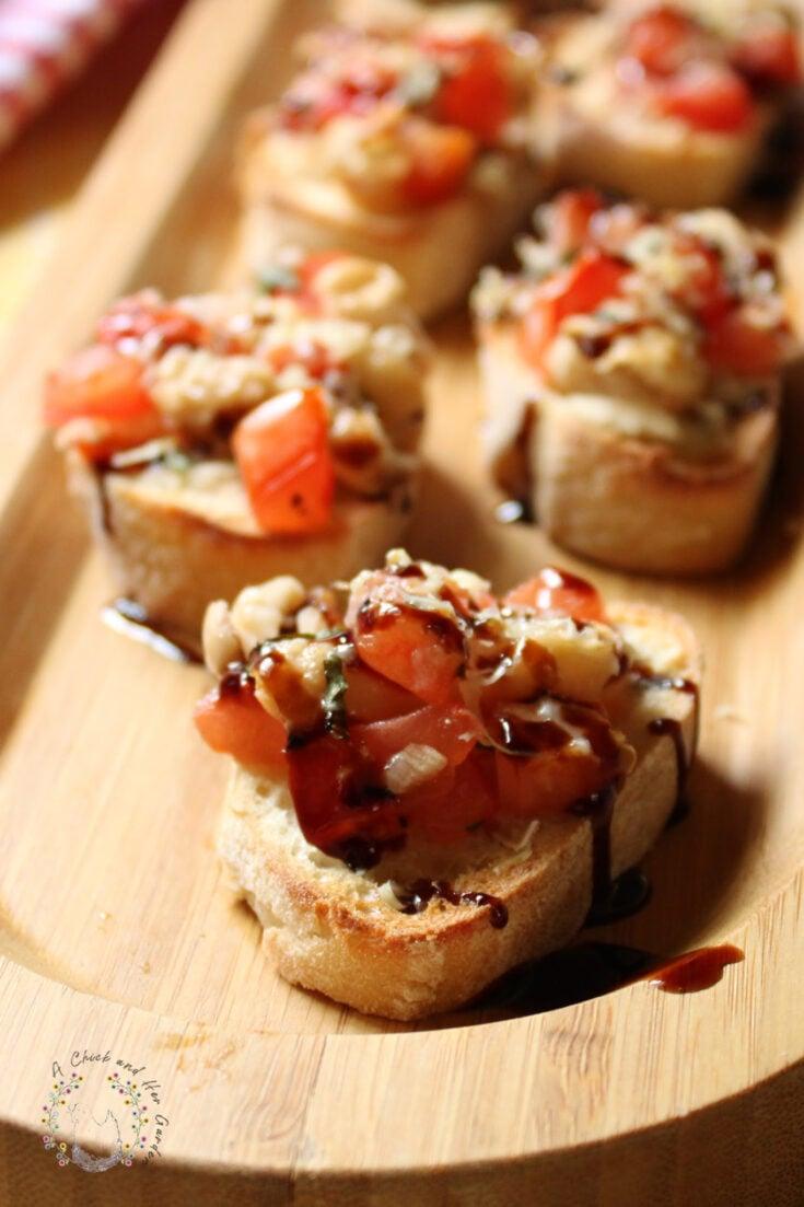 closeup of bruschetta crostini slices on a bamboo tray