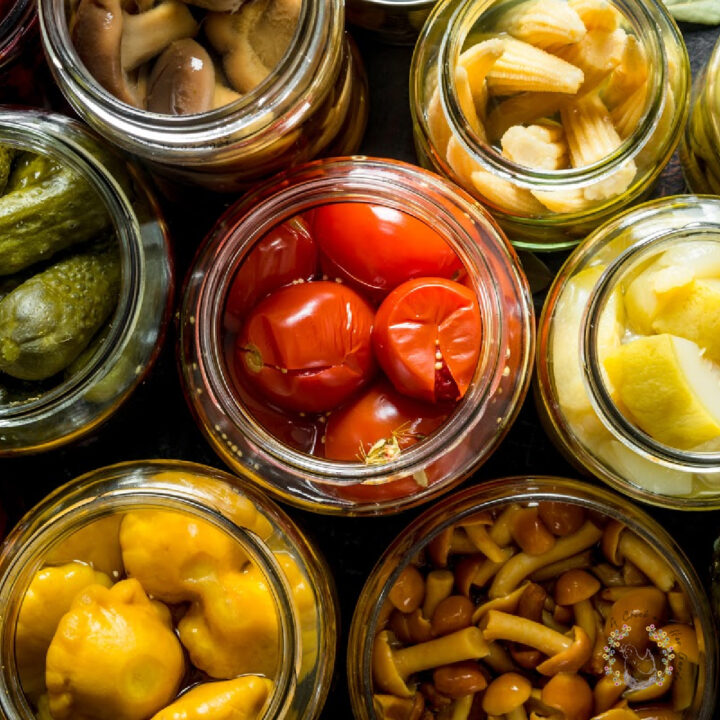 overhead view of glass jars filled with tomatoes, pickles, baby corn, squash and mushrooms